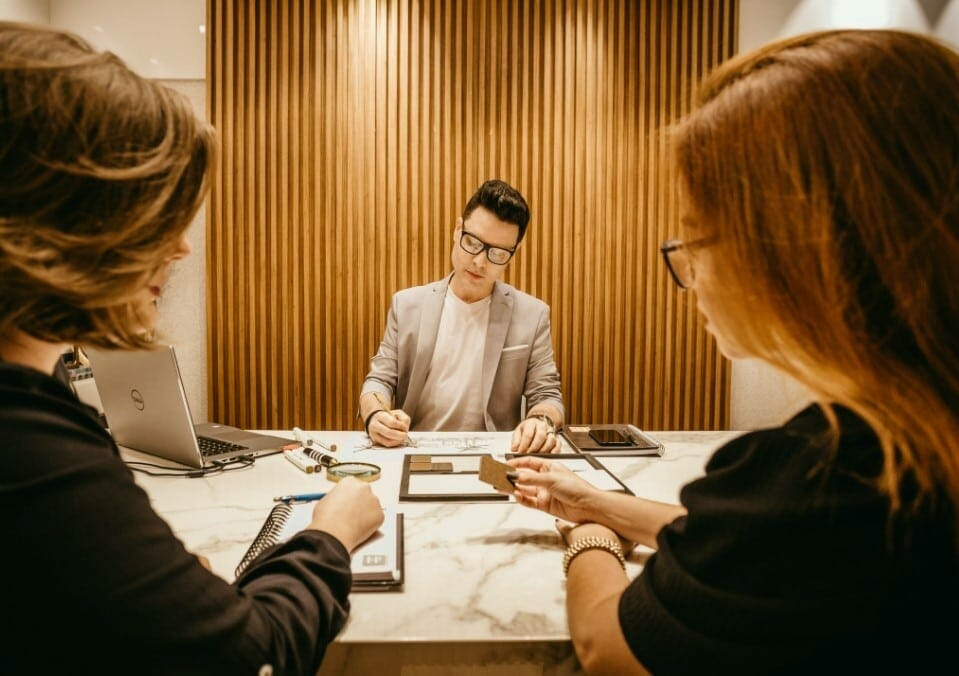 man with glasses signing papers