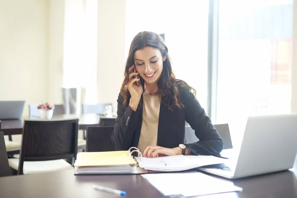 Virtual assistant sitting at her laptop talking to a phone
